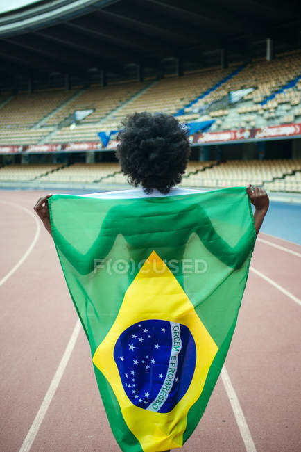 Young female athlete in stadium carrying Brazilian flag — Stock Photo