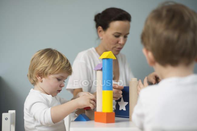 Матері і сини, граючи з іграшкою, будівельна щілинна — стокове фото