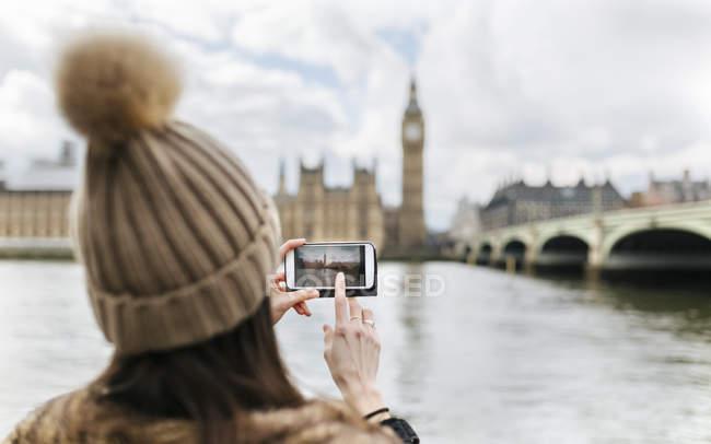 Великобританії, Лондоні, задньої зору молода жінка беручи малюнок Вестмінстерського парламенту — стокове фото