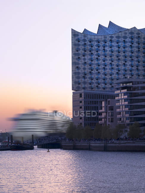Elbphilharmonie and driving cruise liner at sunset, Hamburgo, Alemania - foto de stock