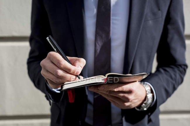 Businessman writing in small diary — Stock Photo