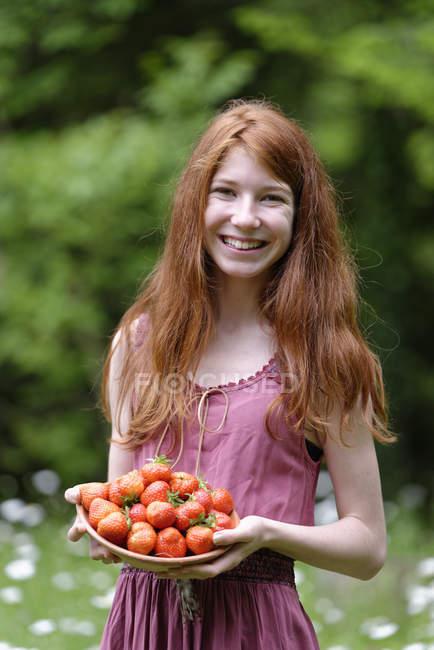 Ritratto di adolescente rossa con ciotola di fragole — Foto stock