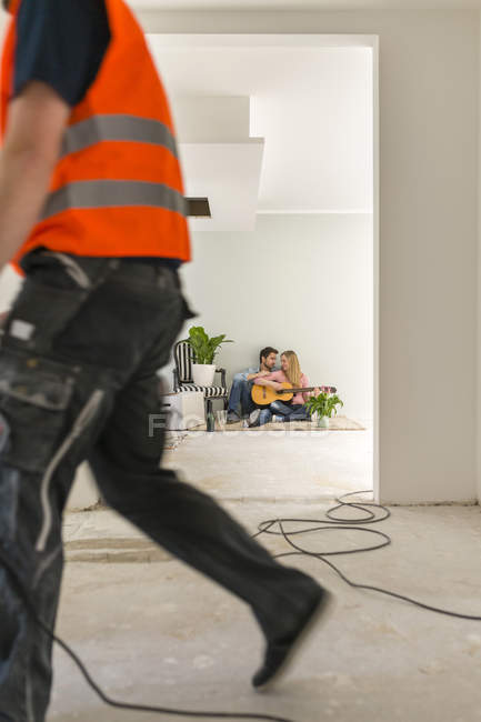 Couple with guitar sitting on the floor of their new home while man working in the foreground — Stock Photo