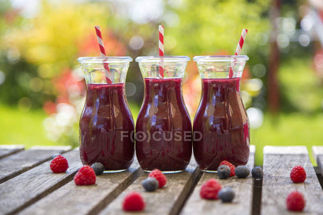 Row of three raspberry blueberry smoothies on garden wooden table — Stock Photo