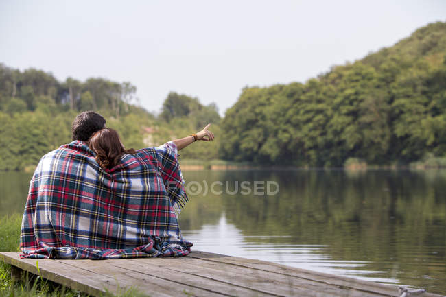 Back view of young couple sitting on a jetty at lake — Stock Photo