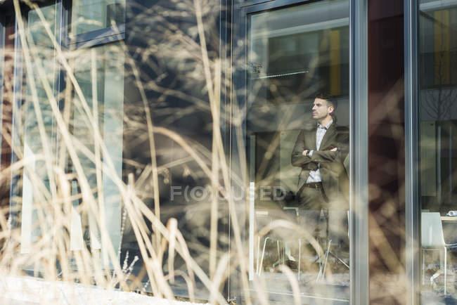 Giovane uomo d'affari che osserva dalla finestra — Foto stock