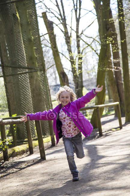 Menina feliz correndo com os braços estendidos — Fotografia de Stock