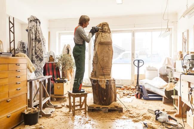 Holzschnitzer in Werkstatt mit Fräse auf Skulptur arbeitet, auf Hocker stehend — Stockfoto