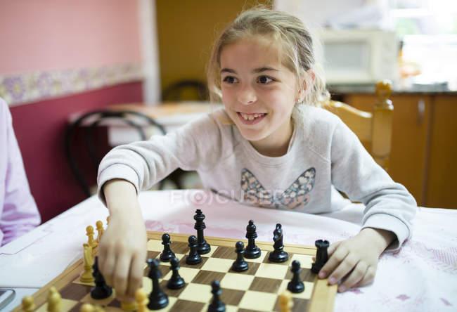 Souriant Petite fille jouant aux échecs — Photo de stock