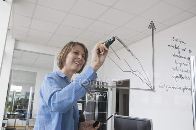 Businesswoman drawing diagram on glass pane in office — Stock Photo