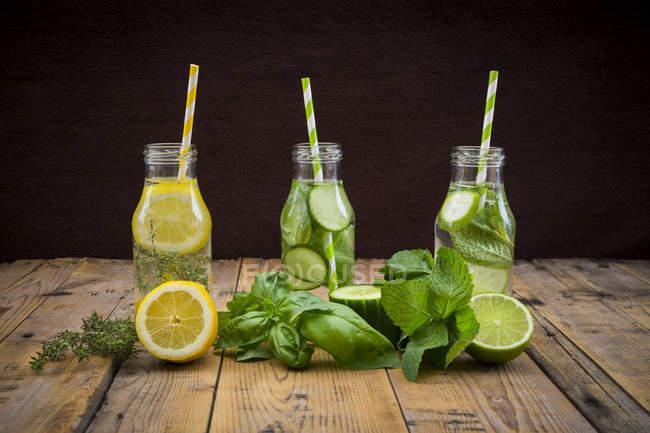 Tre bottiglie di vetro della tabella acqua aromatizzata con erbe e frutti diversi — Foto stock