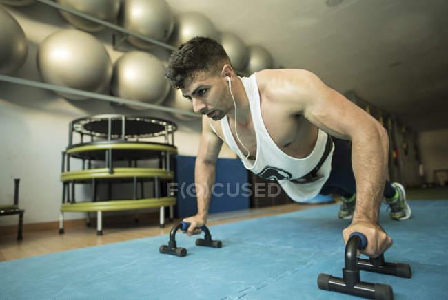 Man doing pushups in gym — Stock Photo