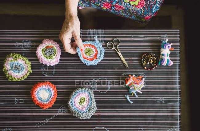Hands of senior woman holding crochet — Stock Photo
