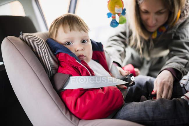 Женщина, крепления сиденья Белл его маленький сын, сидя в кресле ребенка в автомобиле — стоковое фото