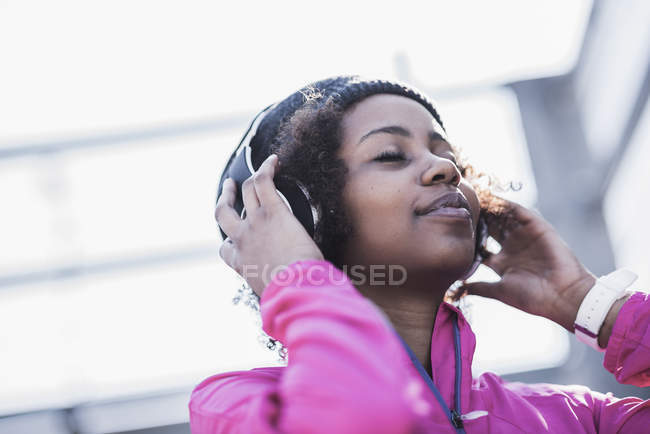 Young woman wearing headphones outdoors — Stock Photo