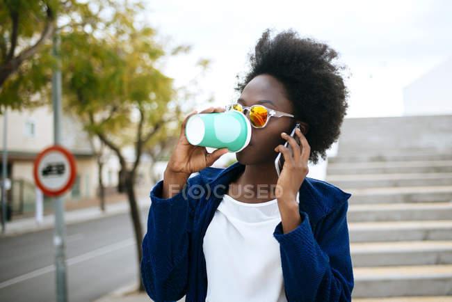 Jovem com café para ir telefonar com smartphone — Fotografia de Stock