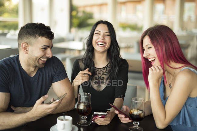 Friends sitting in cafe and having fun — Stock Photo