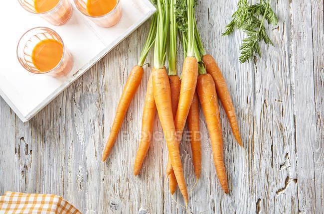 Cenouras e três copos de suco de cenoura na superfície de madeira — Fotografia de Stock