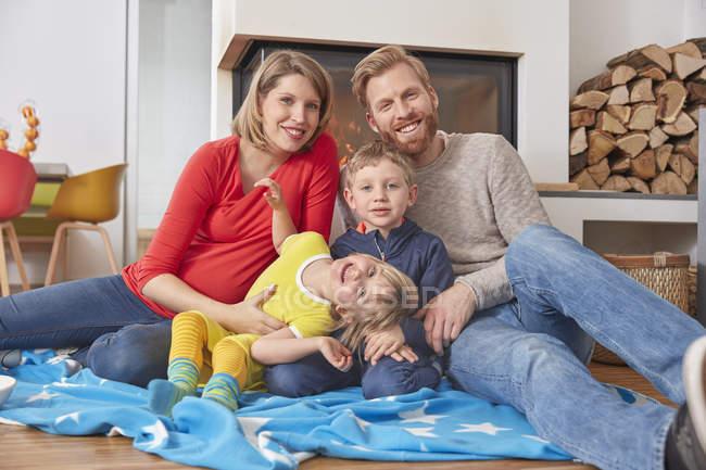Портрет щаслива родина, сидячи на ковдру на підлозі будинку — стокове фото