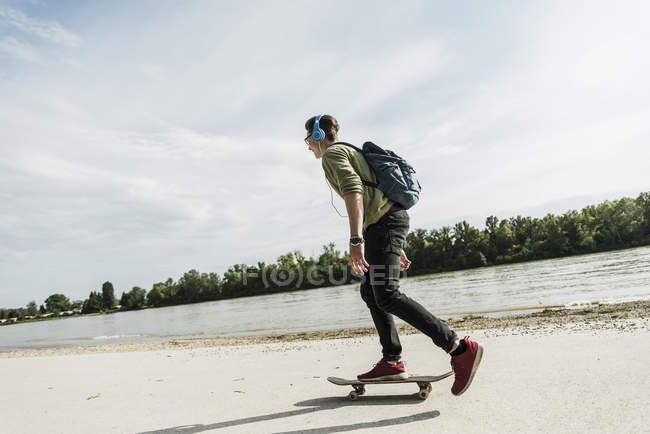 Skateboarding young man with headphones — Stock Photo