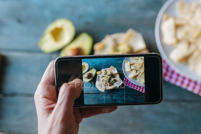 Tomando una foto de nachos y guacamole con smartphone, primer plano - foto de stock