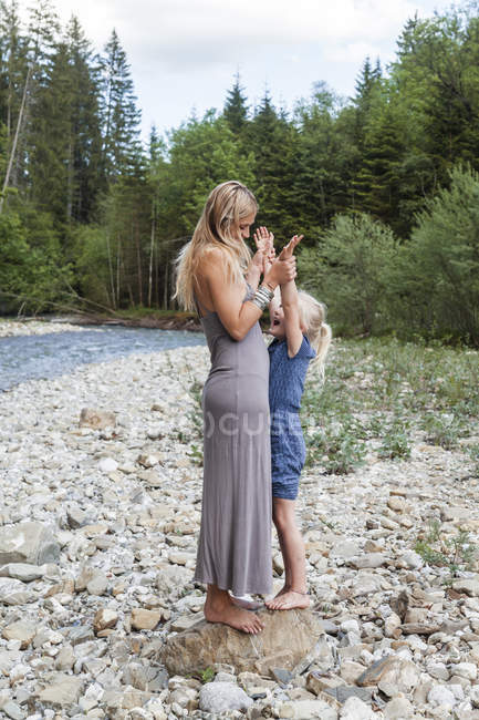 Mother and her little daughter standing together on a rock at riverside — Stock Photo