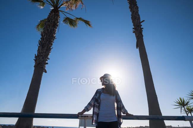 Jovem de pé sob as palmeiras — Fotografia de Stock