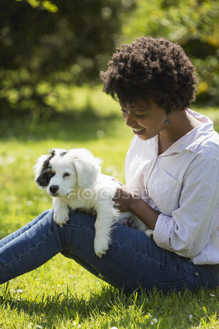 Woman sitting with dog on lap — Stock Photo