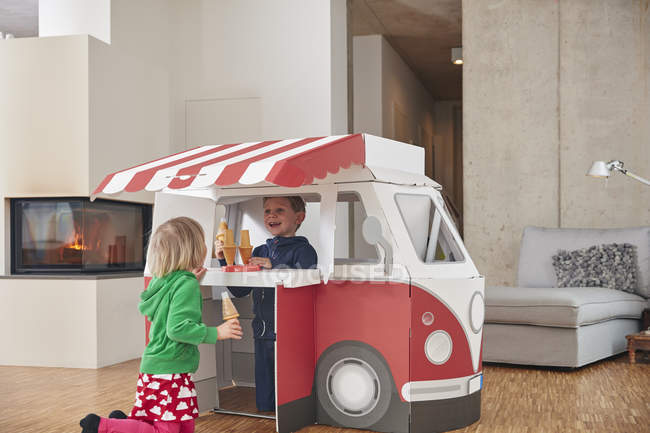 Brother and sister with ice cream and model van in living room — Stock Photo