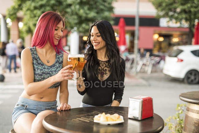Female Friends having beer in bar outdoors — Stock Photo