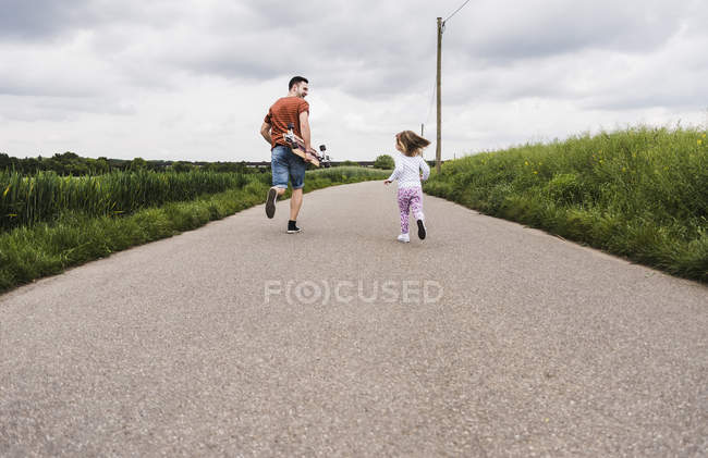 Father with skateboard and daughter running on country lane — Stock Photo