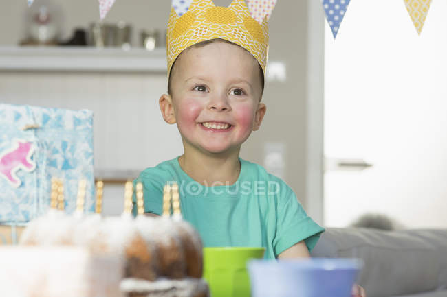 Happy boy wearing paper crown sitting at birthday table — Stock Photo