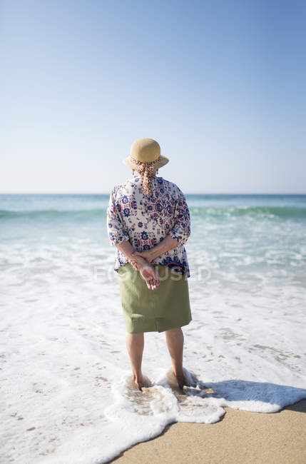 Back view of senior woman standing on the beach — Stock Photo