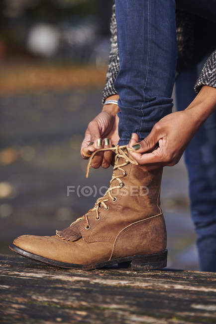 Hands of woman tying boot — Stock Photo