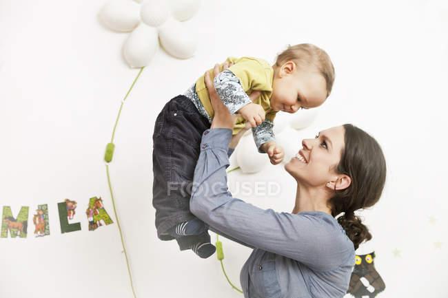 Матері, підіймаючи її малюк на дому — стокове фото
