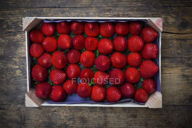 Wooden box with sorted strawberries — Stock Photo