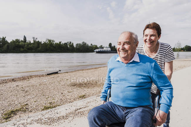 Woman pushing her old father sitting on wheeled walker — Stock Photo