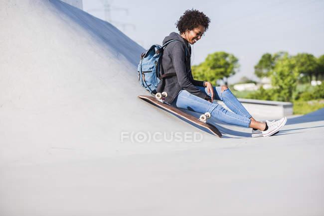 Sorrindo jovem mulher sentada com skate ouvindo música — Fotografia de Stock