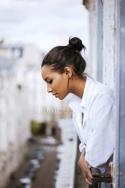 Франция, Париж, молодая женщина, выглядывающая из окна, глядя вниз — стоковое фото