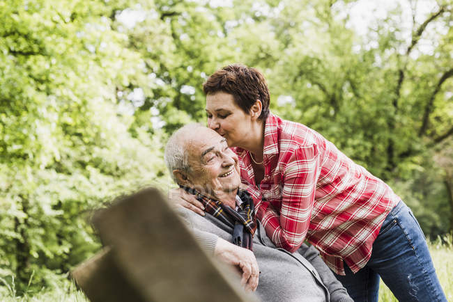 Happy woman kissing her old father sitting on a bench in nature — Stock Photo