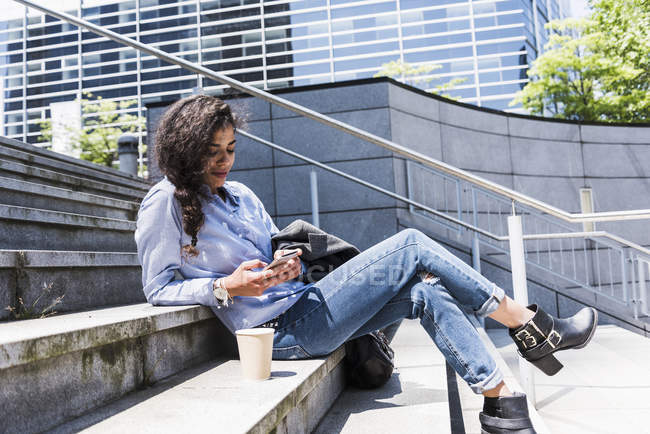 Young woman sitting on stairs looking at cell phone — Stock Photo