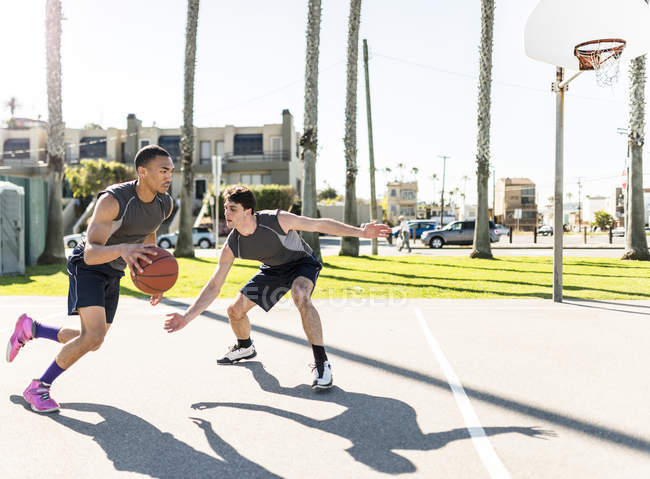 Young men playing basketball on outdoor court — Stock Photo