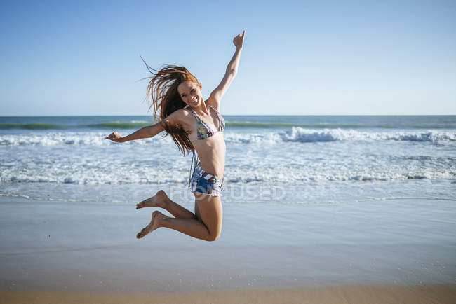 Enthusiastic young woman jumping on beach — Stock Photo