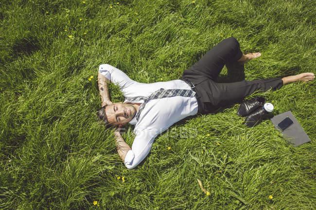 Homme d'affaires couché dans la prairie — Photo de stock