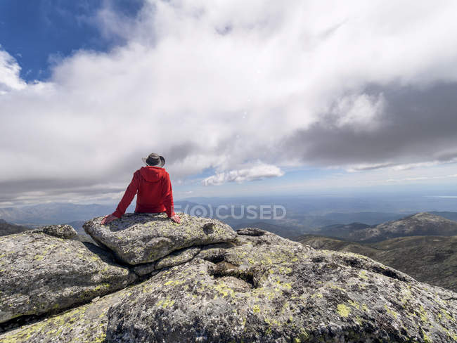 Spain, Sierra de Gredos, Rear view of hiker sitting on rock, scenic mountains landscape on background — Stock Photo