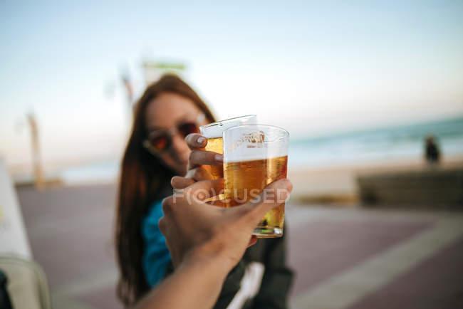 Крупный план женщин, звонящих пивными стаканами на открытом воздухе — стоковое фото