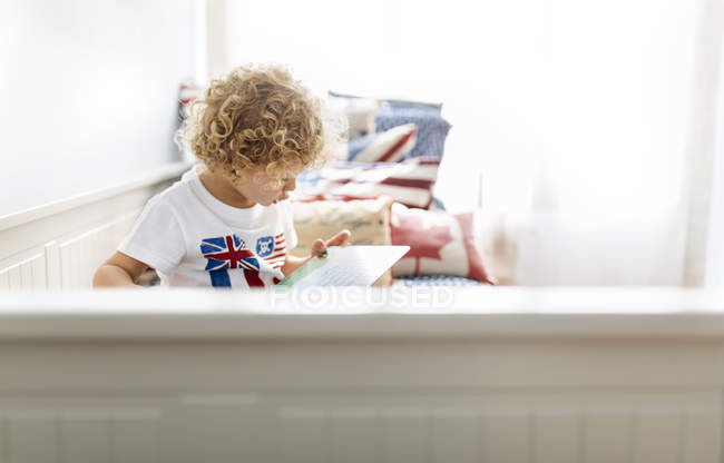 Little caucasian boy watching picture book at home — Stock Photo