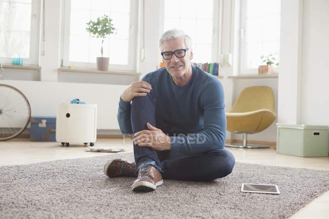 Reifer Mann zu Hause entspannt sitzen auf Boden — Stockfoto