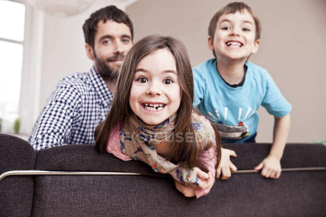 Portrait of grinning little girl at home with father and brother in the background — Stock Photo