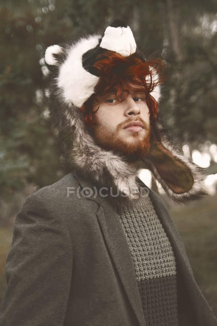 Portrait of redheaded young man wearing raccoon hat in the woods — Stock Photo